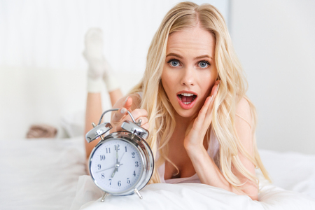 shocked young woman with alarm clock lying on bed and looking at camera Stock Photo