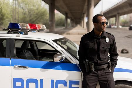 Afroamerikanischer Polizist lehnt sich zurück auf Auto und schaut weg
