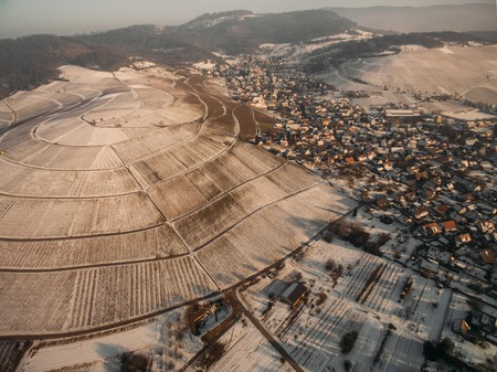 aerial view of beautiful snow-covered fields and houses at winter morning, Germany