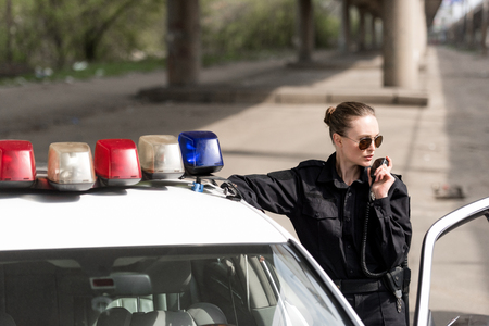 policewoman talking by radio set near patrol car Stock Photo