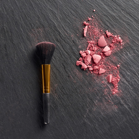Pink blush pieces and brush on dark slate background Stock fotó