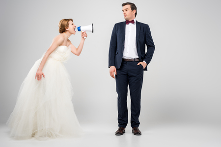 angry bride with megaphone yelling at groom, isolated on grey, feminism concept 免版税图像