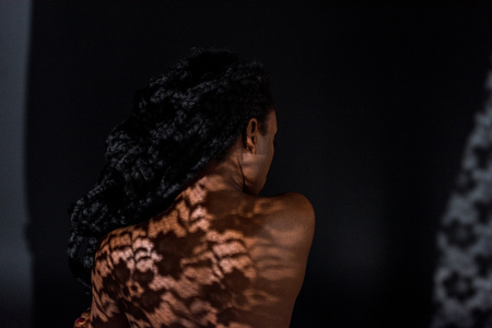 rear view of young african american woman with shadow on naked back