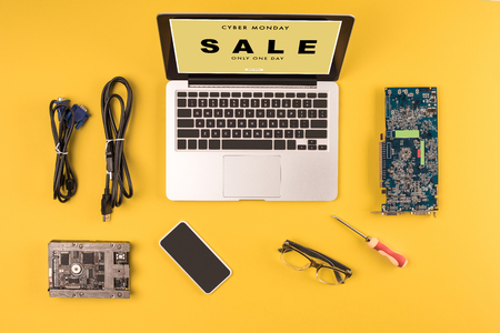top view of laptop with inscription cyber monday sale only one day, smartphone, eyeglasses and wires on yellow