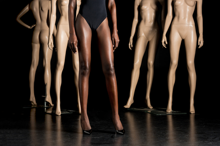 cropped shot of african american woman in high heeled shoes standing between mannequins on black