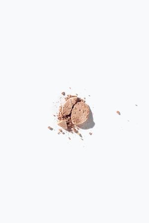 Broken face powder on white background
