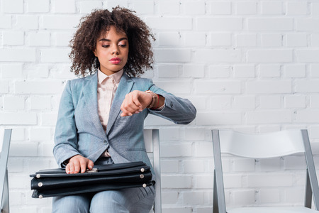 Businesswoman in suit holding briefcase and checking her watch Stock Photo