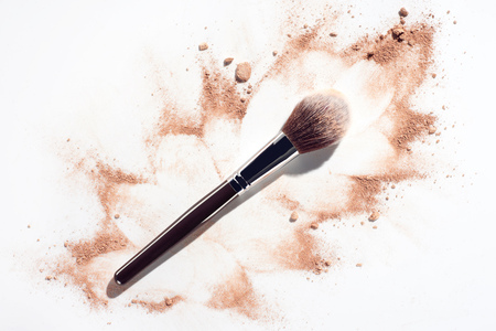 Plush make up brush on white background with scattered face powder