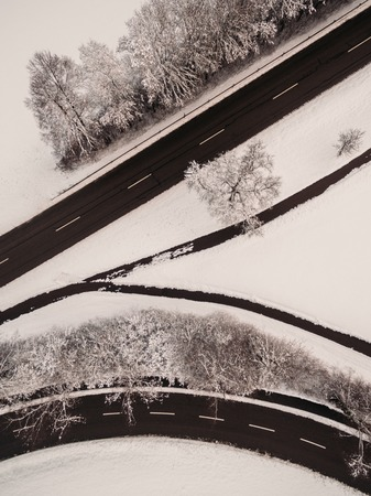 aerial view of empty asphalt road and snow-covered trees at winter, Germany