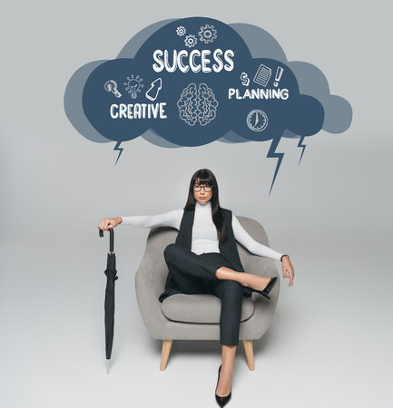 beautiful brunette businesswoman sitting on armchair with umbrella on gray, cloud with creative, success and planning inscription above Banco de Imagens