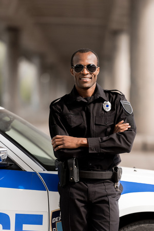 smiling african american police officer with crossed arms leaning back on car and looking at camera Stockfoto