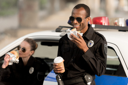 african american policeman with paper cup of coffee eating burger while his female partner eating burger in car