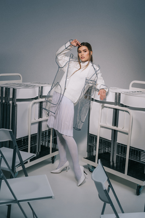 stylish woman in white clothing and raincoat posing with collapsible chairs behind on grey background Stock fotó - 110772278