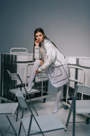 fashionable woman in white clothing and raincoat posing with collapsible chairs behind on grey background Stock fotó - 110772293