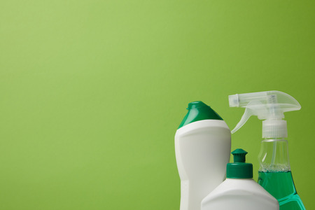 bottles and spray for spring cleaning isolated on green