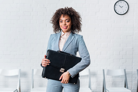 African american businesswoman in suit holding briefcase