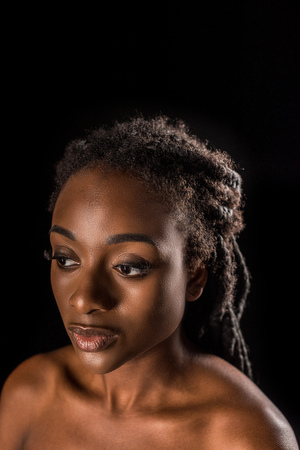 portrait of beautiful young african american woman looking away isolated on black