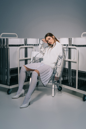 fashionable woman in white clothing posing with collapsible chairs behind on grey background Stock fotó