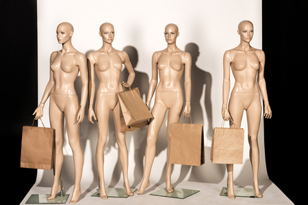 bald mannequins with shopping bags on white
