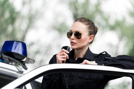 Atractiva mujer policía hablando por radio cerca del coche de policía Foto de archivo