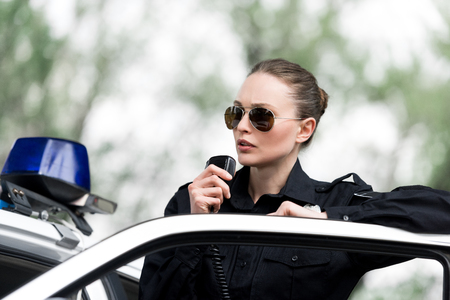 attractive policewoman talking by radio set near police car