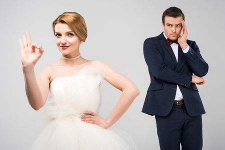 bride in wedding dress showing ok sign while worried groom standing behind, isolated on grey, feminism concept