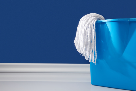 rag and bucket for spring cleaning on blue