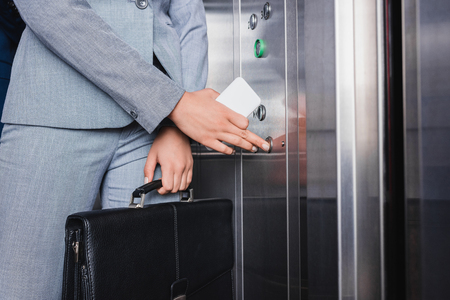 Close-up view of woman in suit holding electronic key and pushing button in elevator