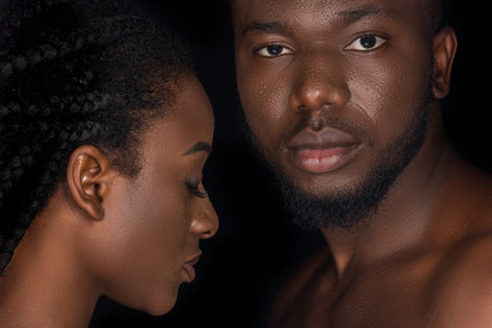 beautiful young african american couple with water drops on faces posing isolated on black Archivio Fotografico