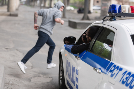 african american policeman on car chasing thief Stok Fotoğraf