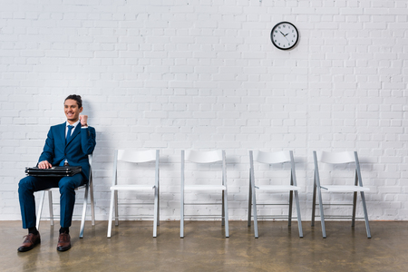 Concept of successful interview with young happy businessman sitting on chair