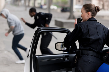 policewoman talking by radio set while her partner chasing thief