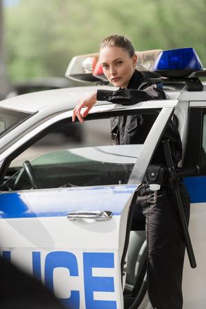 policière souriante debout près de la voiture de police sous le pont en regardant la caméra