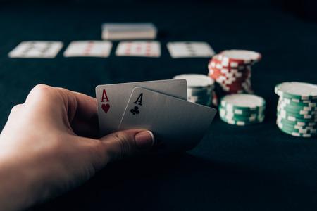 Mujer sosteniendo naipes por mesa de casino