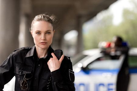 policière utilisant un talkie-walkie et regardant la caméra avec un partenaire flou près de la voiture en arrière-plan