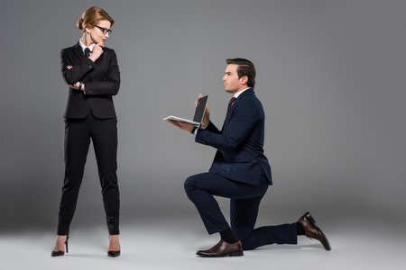 businessman on one knee holding laptop for feminist businesswoman, isolated on grey Archivio Fotografico - 110781357
