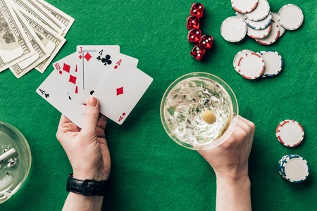 Woman with alcohol in glass playing poker game by casino table Stock Photo