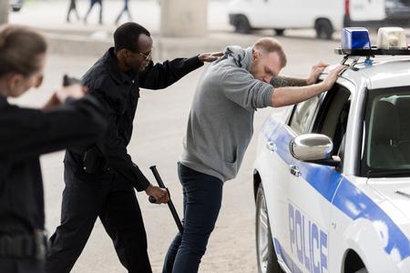 Vista lateral del afroamericano arrestar al hombre mientras la mujer policía le apunta con una pistola