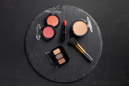 Template with cosmetics and brush on round slate background Stock Photo
