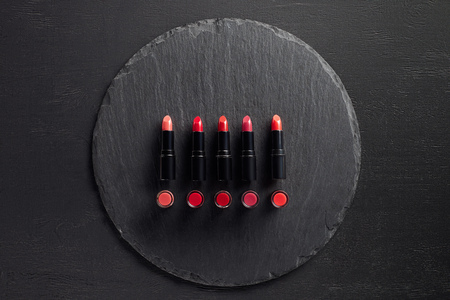 Row of red lipsticks on round slate background