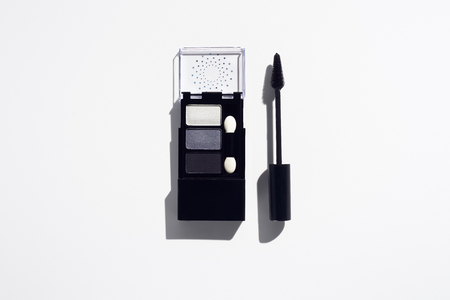 Grey eye shadows and mascara brush on white background