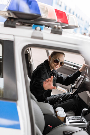 smiling female police officer sitting in patrol car Stock Photo