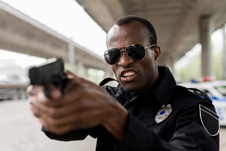 angry african american policeman shouting and aiming by handgun Stock Photo