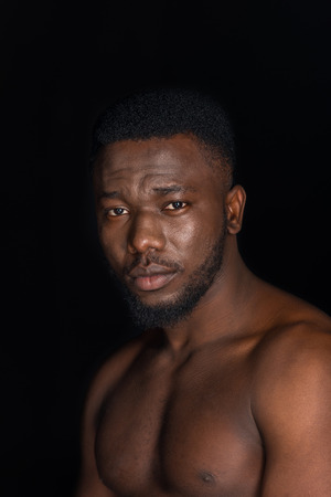 handsome young bare chested african american man looking at camera isolated on black