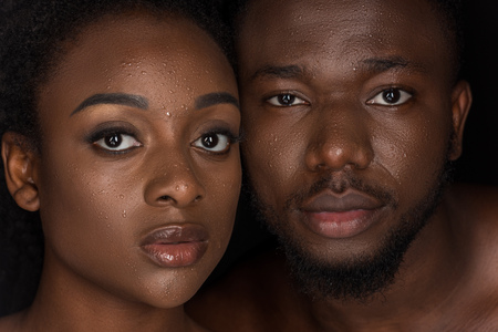 young african american couple with water drops on faces looking at camera on black