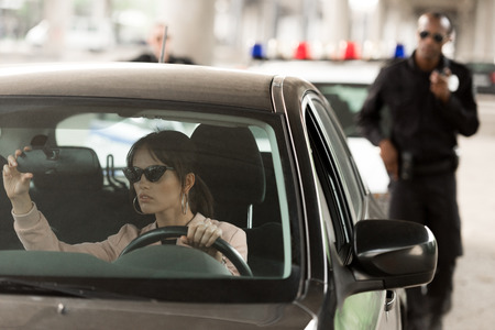 african american policeman approaching to car of young woman in sunglasses Stock Photo