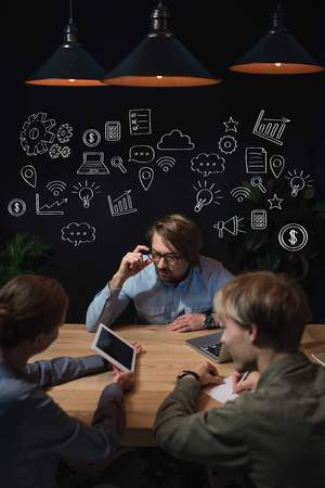 Businesswoman showing something on tablet to her partners and sitting at table, with hand-drawn business icons over heads