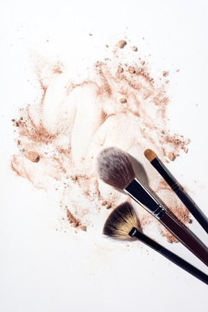 Foundation smears and make up brushes on white background