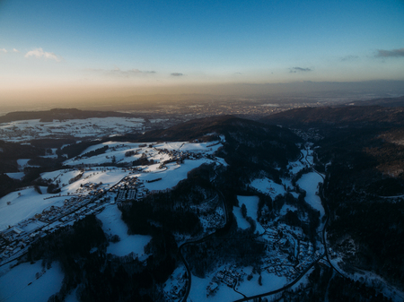 aerial view of beautiful winter landscape with hills, trees and rooftops, Germany