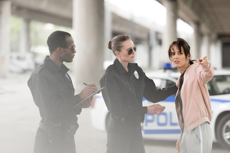 young worried woman pointing by finger to policewoman and policeman writing in clipboard